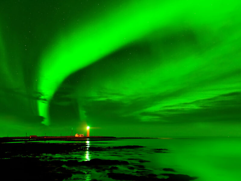 A look at The Northern Lights, shining green over the Grotta Lighthouse at night.