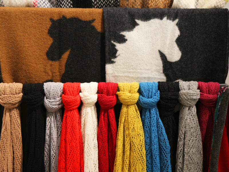 A selection of scarves, laid out by color. Two of the scarves depict a horse design.