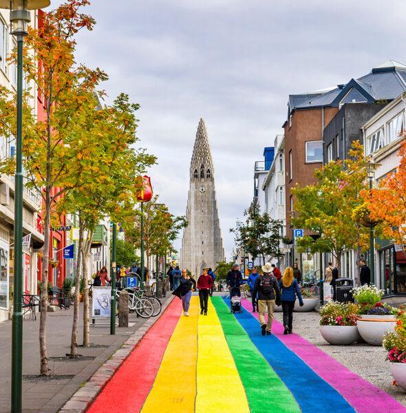 People walk the rainbow painted road in Reykjavik Iceland