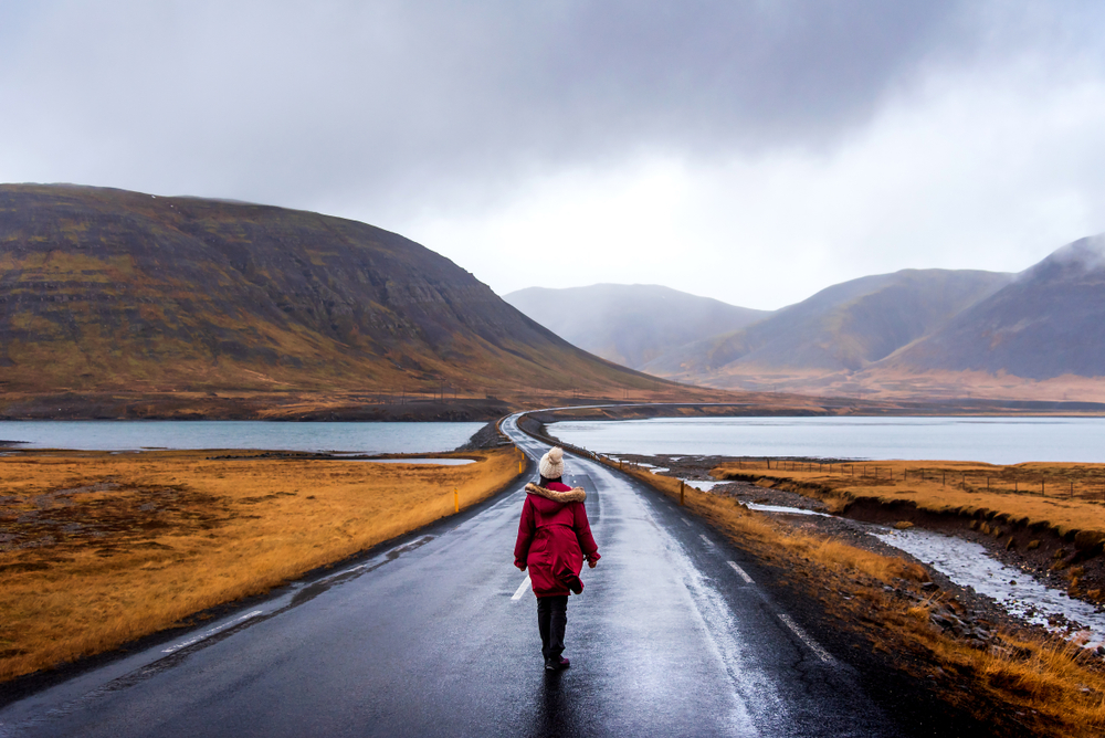 Photo of a girl on a road. Summer is the best time to visit Iceland to explore.