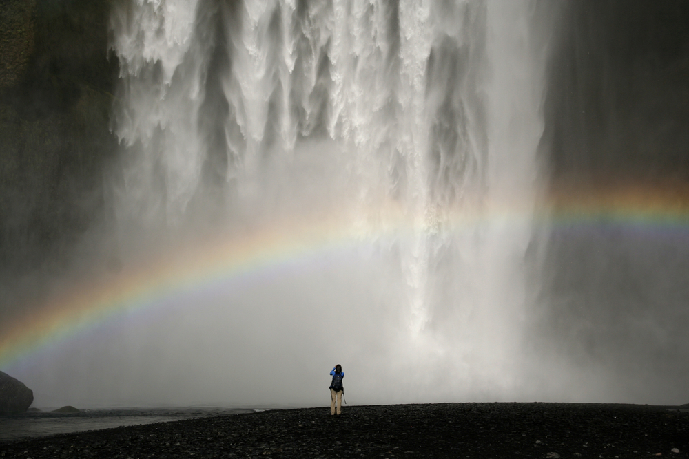 Photo of someone standing in front of a waterfall in Iceland.