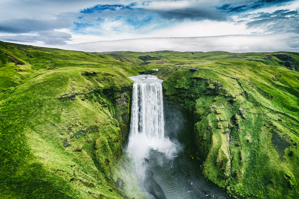Skogafoss waterfall in lush surroundings is one of the best  Iceland tour stops