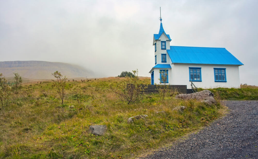 Kirkjubaer Church is a pretty pastel blue church in Iceland
