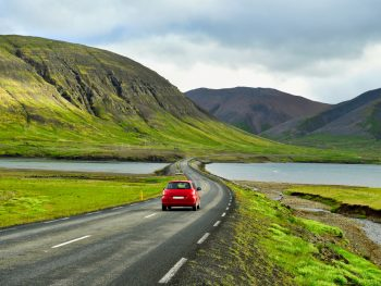 red car driving in iceland among the fjords