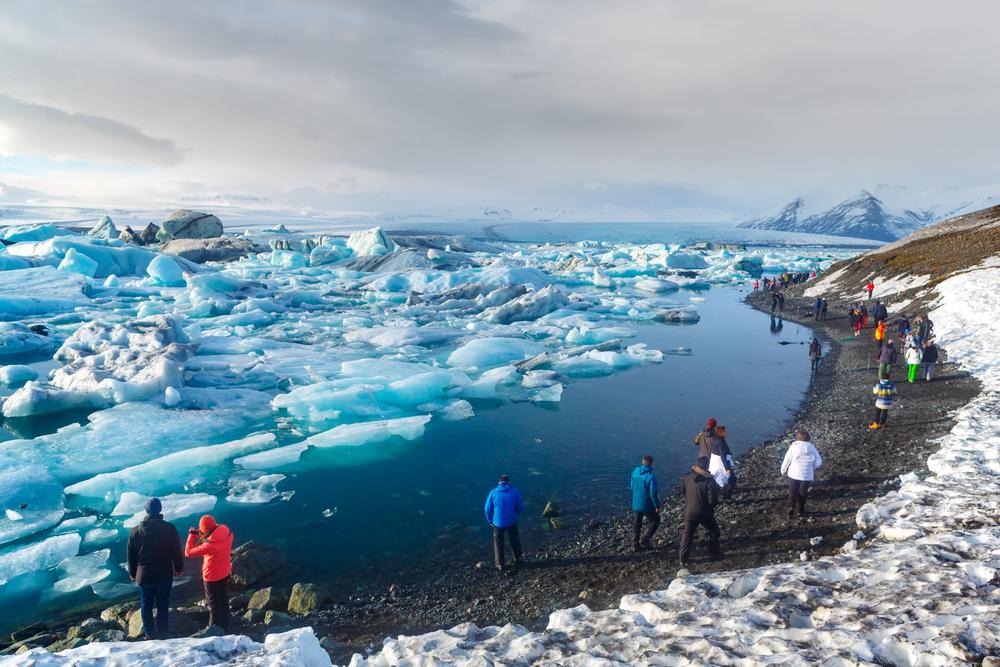 People walking on the shore at jokulsarlon glacier lagoon