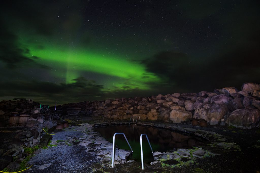 northern lights over grettislaug hot springs north iceland
