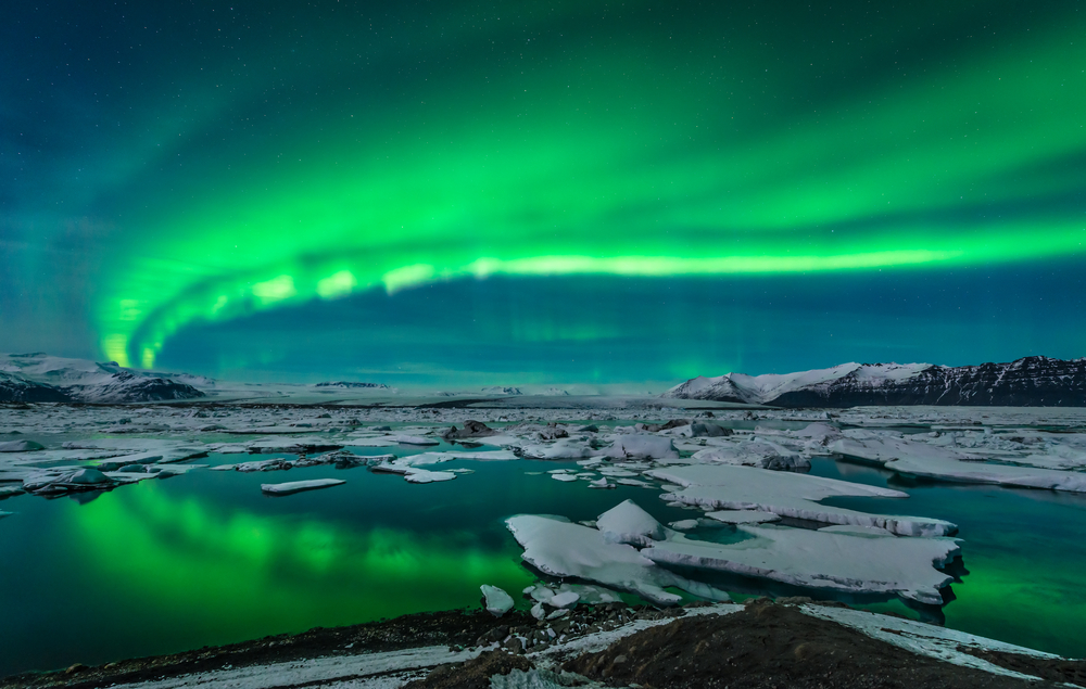 The glowing green of the northern lights in Iceland encompasses the horizon of the ice and coast.