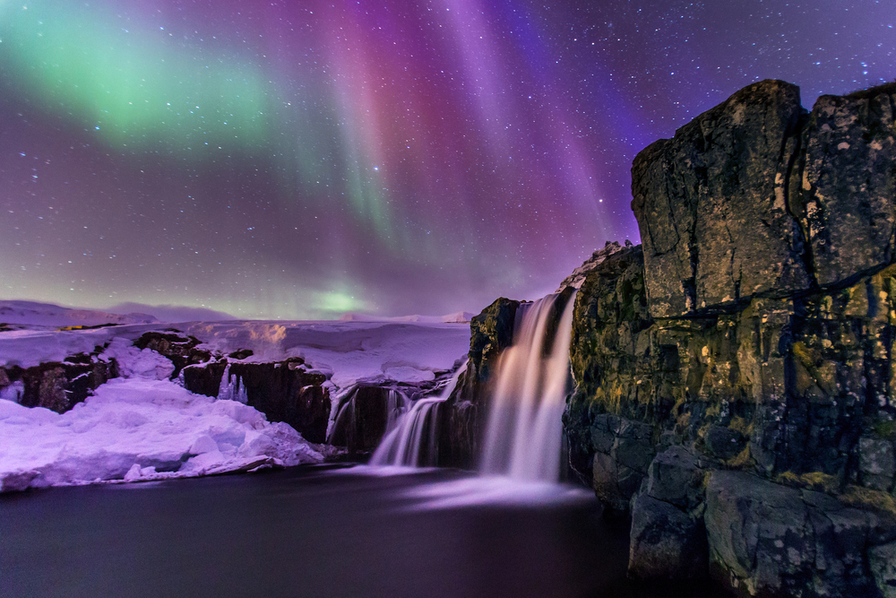 Tours to see the northern lights in Iceland can take you to special spots, such as nearby waterfalls, like in this photo!