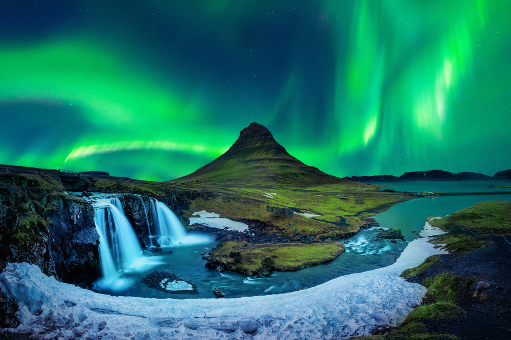 The dancing northern lights in Iceland are only more stunning over the waterfall and mountain views.