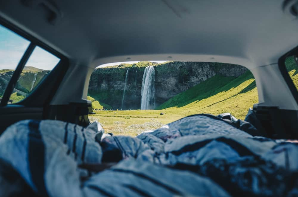 people camping in their car rental in iceland by a waterfall