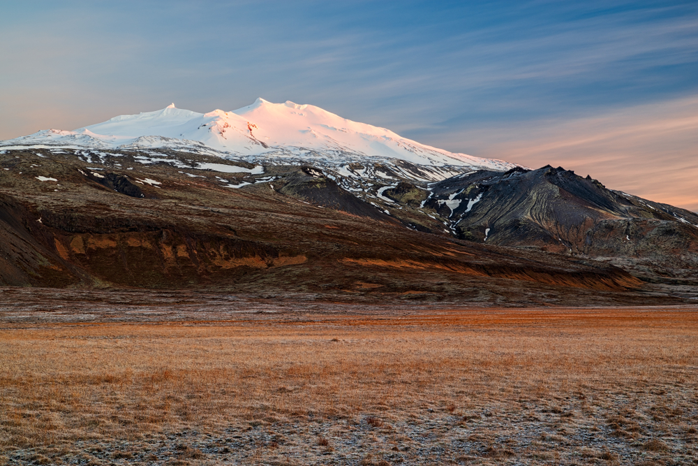 photo of the Snaefellsjokull mountain. There is snow on the top of it.