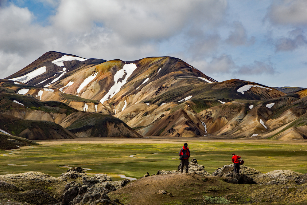 photo of two hikers on the Laugavegur trail which you can hike when you visit iceland national parks. There are mountains in the background.