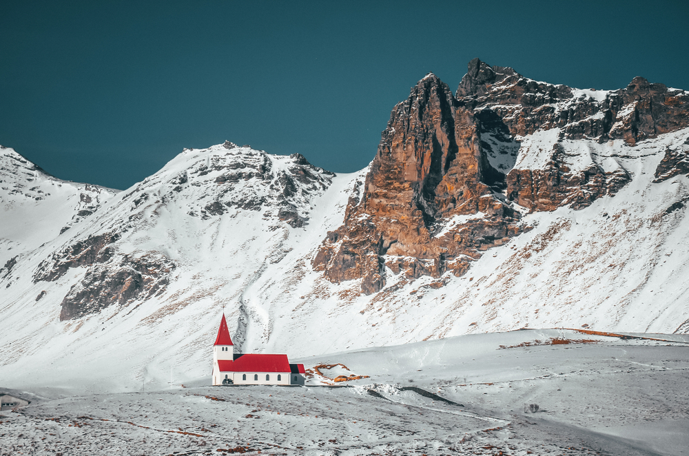 a church in Iceland with snowy mountains in the background