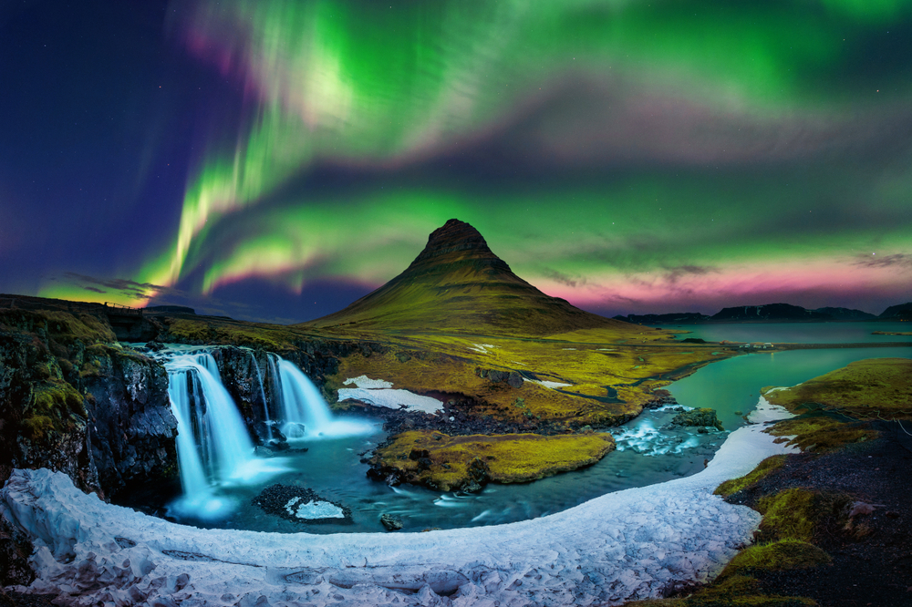 The Northern Lights framing a mountain with a waterfall in the foreground.