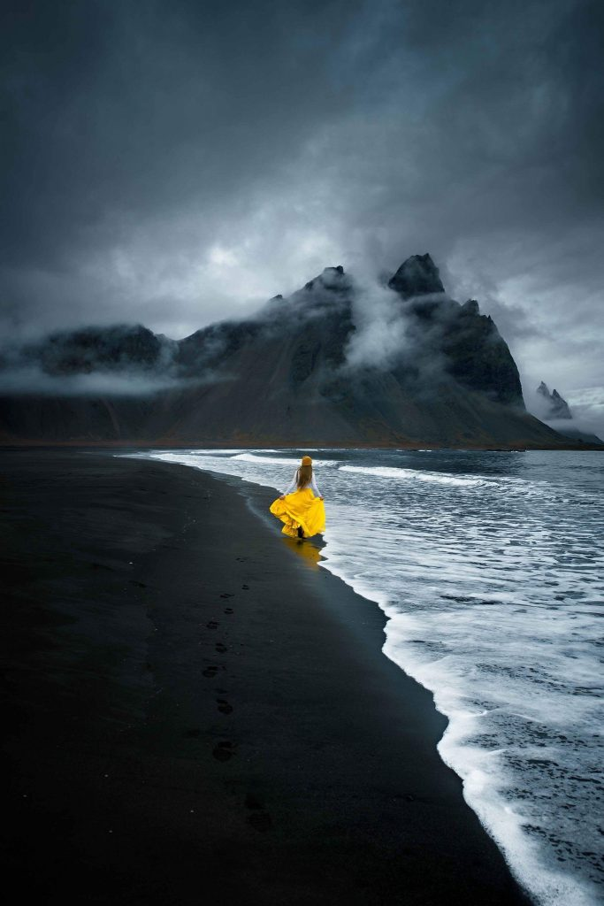 woman in bright yellow on black sand beach by Vestrahorn mountain