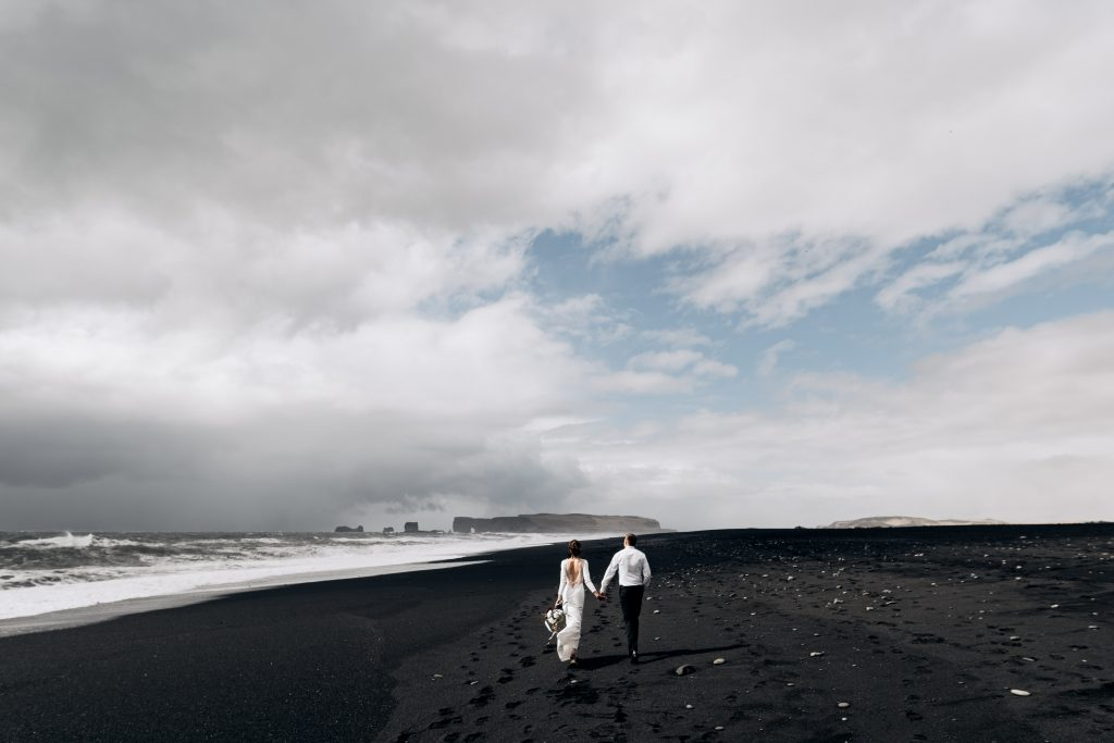 newly married couple walking down black sand beach together Iceland wedding
