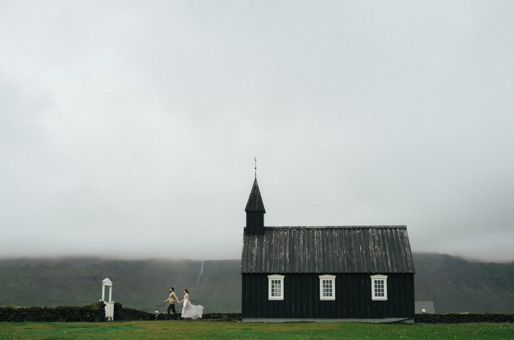 just married couple dashing out of black church with white windows
