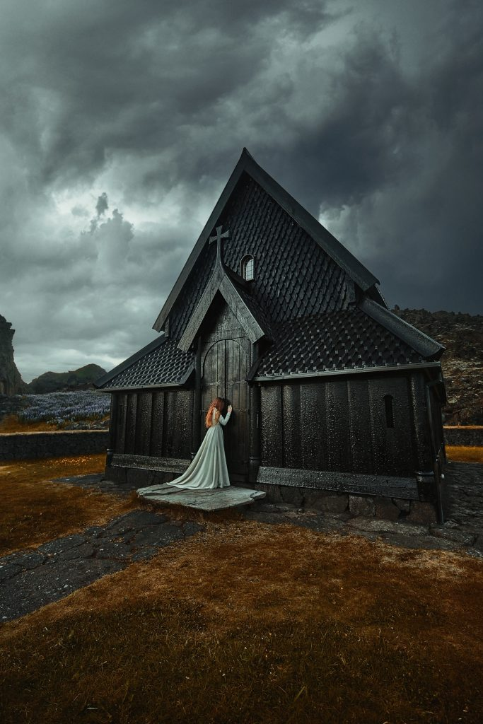 woman weeping against black church on overcast day