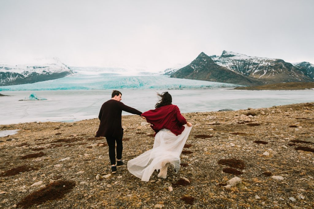 newly married couple running near glacier Iceland wedding