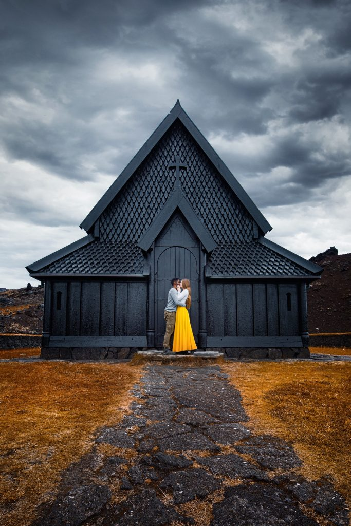 couple kissing in front of stark black church Iceland weddings
