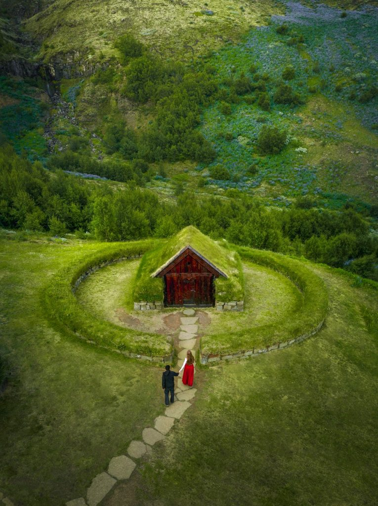 couple walking hand in hand into small, grass roof house Iceland wedding