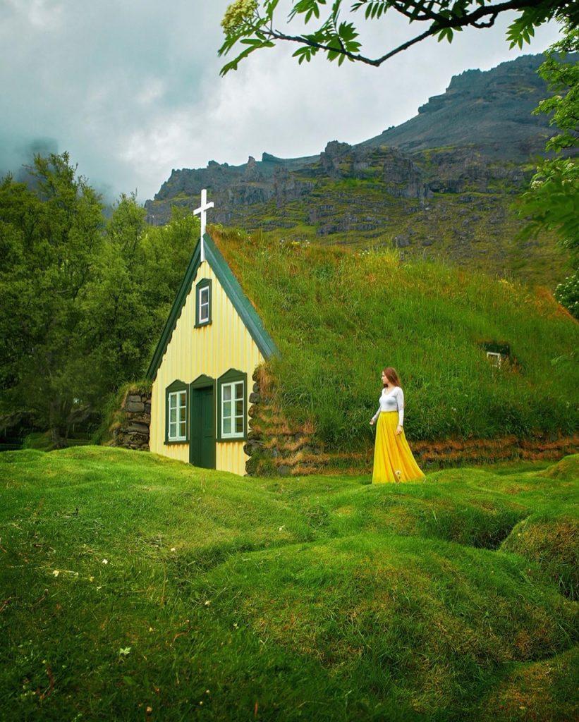 woman standing beside grass roofed church