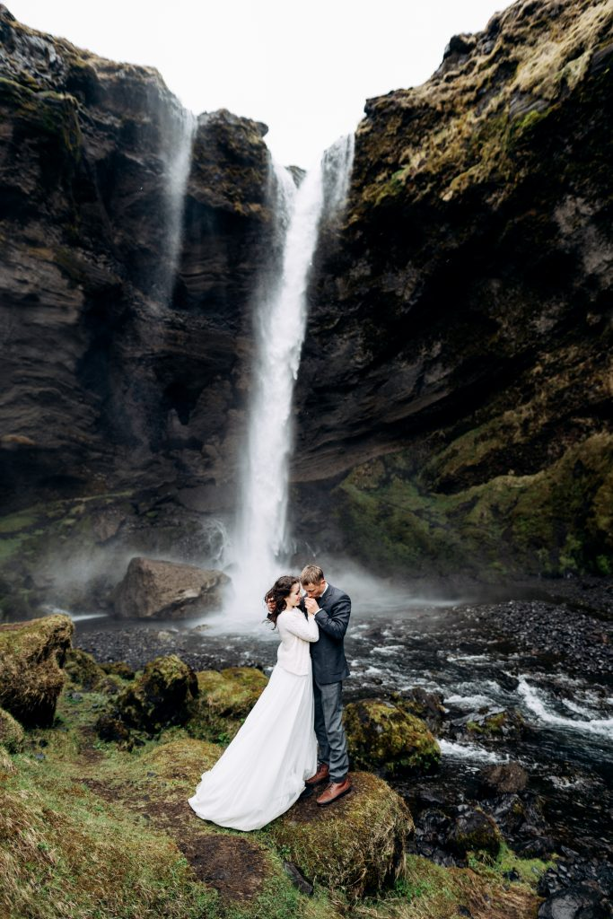 wedding couple standing in front of cascading waterfall Iceland wedding