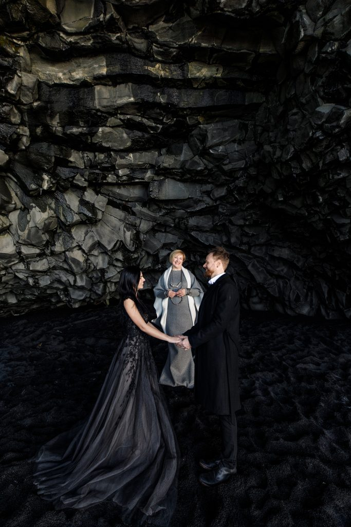 couple being married by female officiant in basalt column cave Iceland wedding
