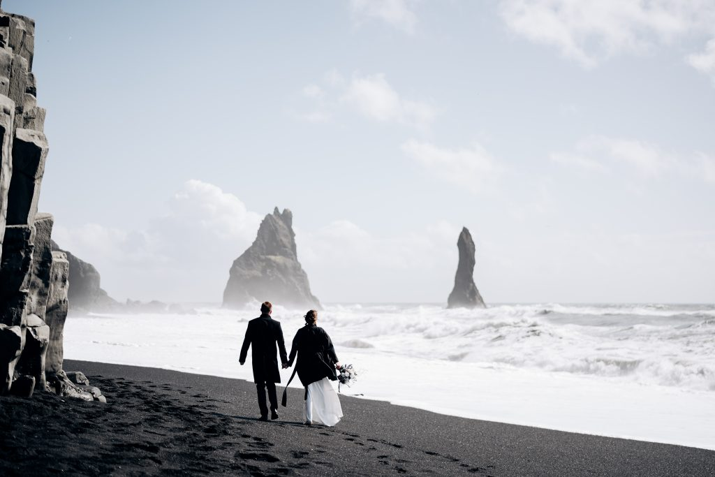 wedding couple strolling along black sand beach Iceland wedding
