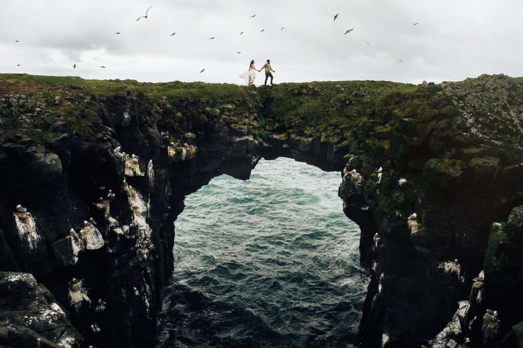 couple crossing rock arch bridge in ocean together Iceland wedding