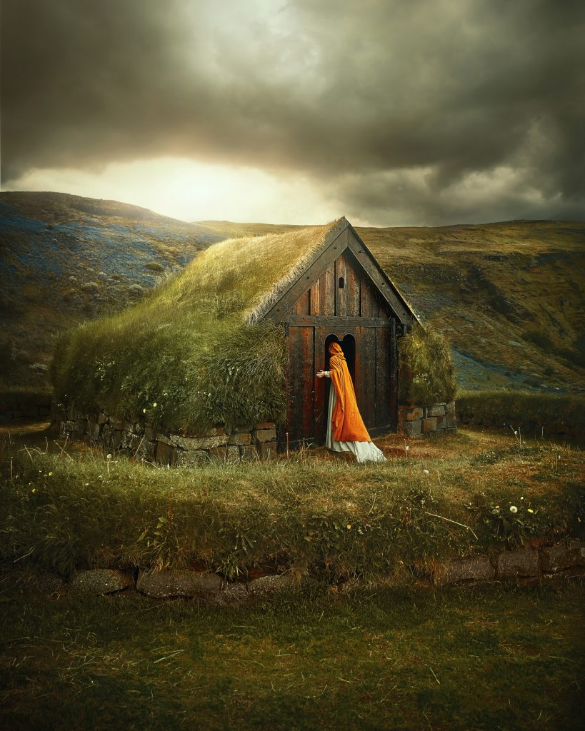 woman in white dress and orange coat peering into grass roof building Iceland wedding