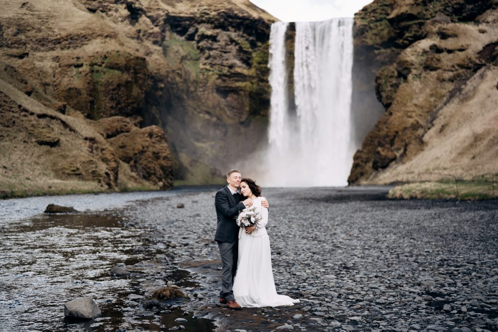 couple in wedding attire in front of powerful waterfall Iceland wedding