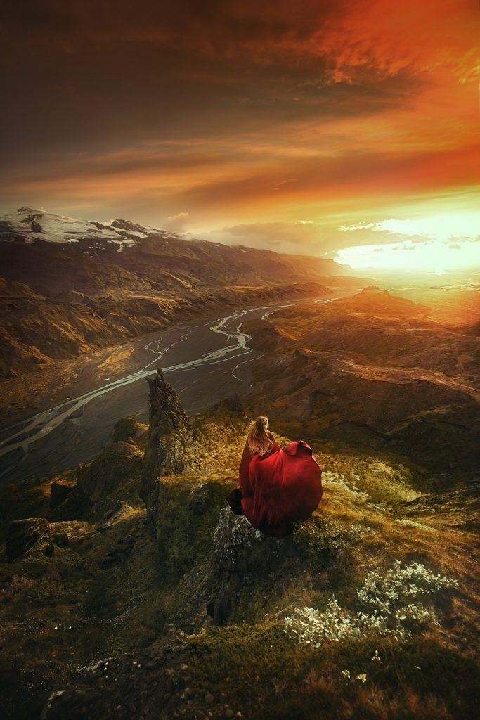 woman in flowing red dress over valley with flowing rivers Iceland wedding