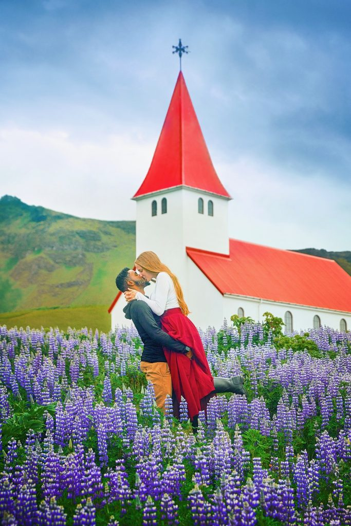 couple kissing in field of purple flowers in front of red roofed church Iceland wedding