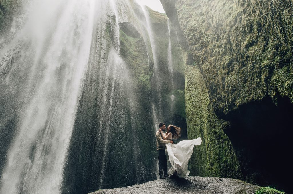 couple in wedding attire standing in front of waterfall, hair and dress flowering Iceland wedding