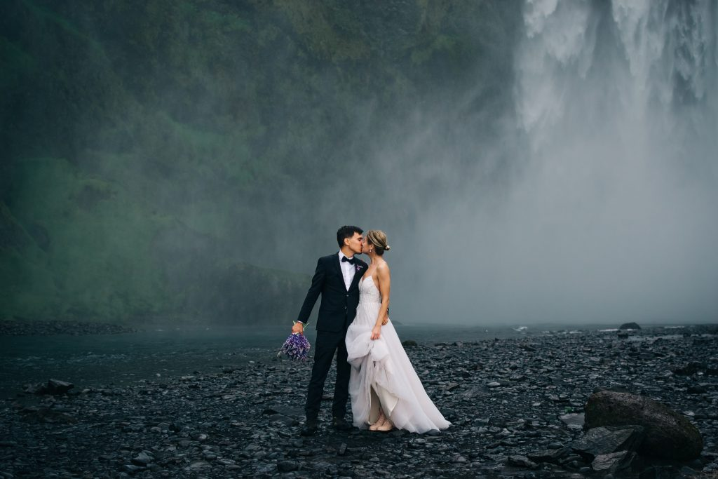 newly married couple kissing in front of Iceland waterfall