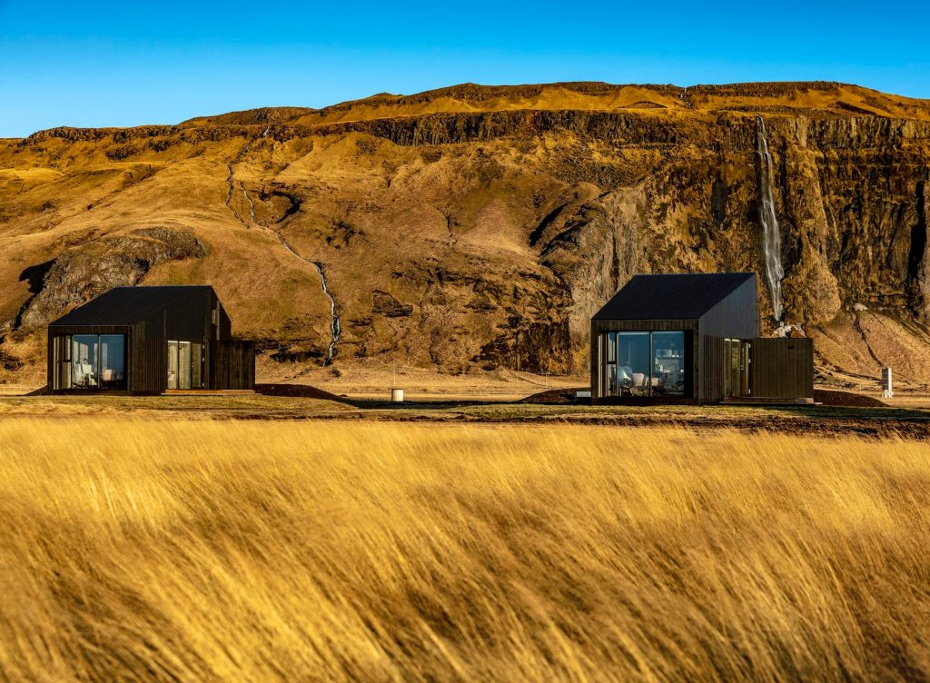 Black cottages in open field airbnbs in iceland