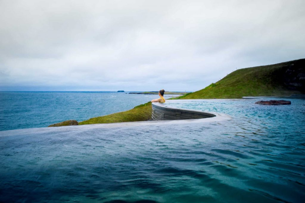 woman leaning over the edge of a geothermal pool in iceland
