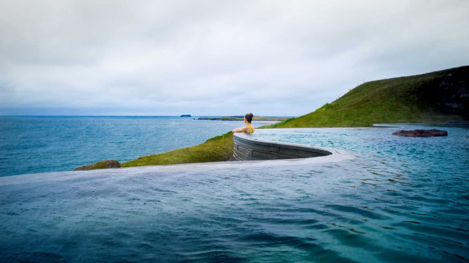 woman swimming in hot pool in iceland overlooking the ocean