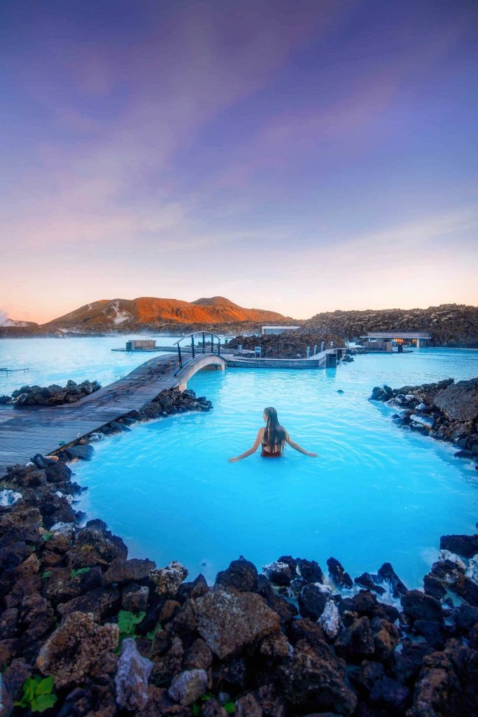 woman standing in the blue waters of the blue lagoon hot springs in iceland