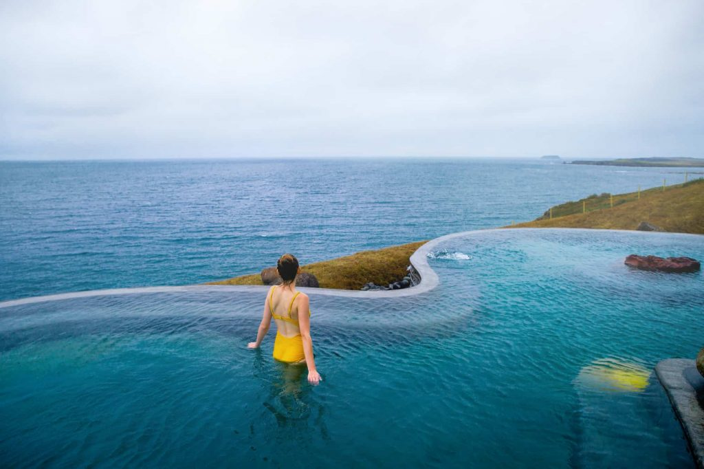 woman standing in yellow bathing suit in a pool at geosea icelandic hot springs overlooking the ocean