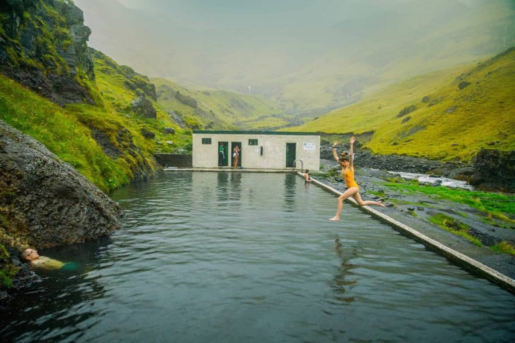 woman in yellow bathing suit jumping into a pool called seljavallalaug hot springs in iceland