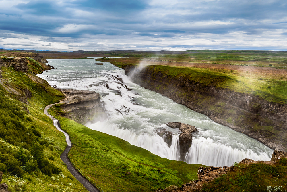 gullfoss waterfall in summer on a cloudy day with green grass all around