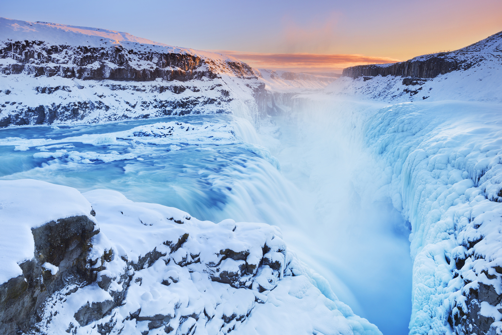 gullfoss waterfall with a lot of snow in winter at sunset