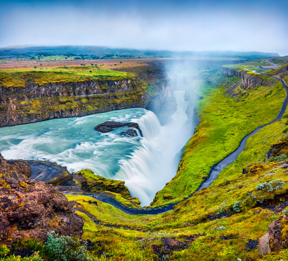 Iceland's gullfoss waterfall plunging into canyon on a cloudy day with green grass