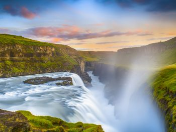 Gullfoss Waterfall in Iceland on a sunny day with green grass all around