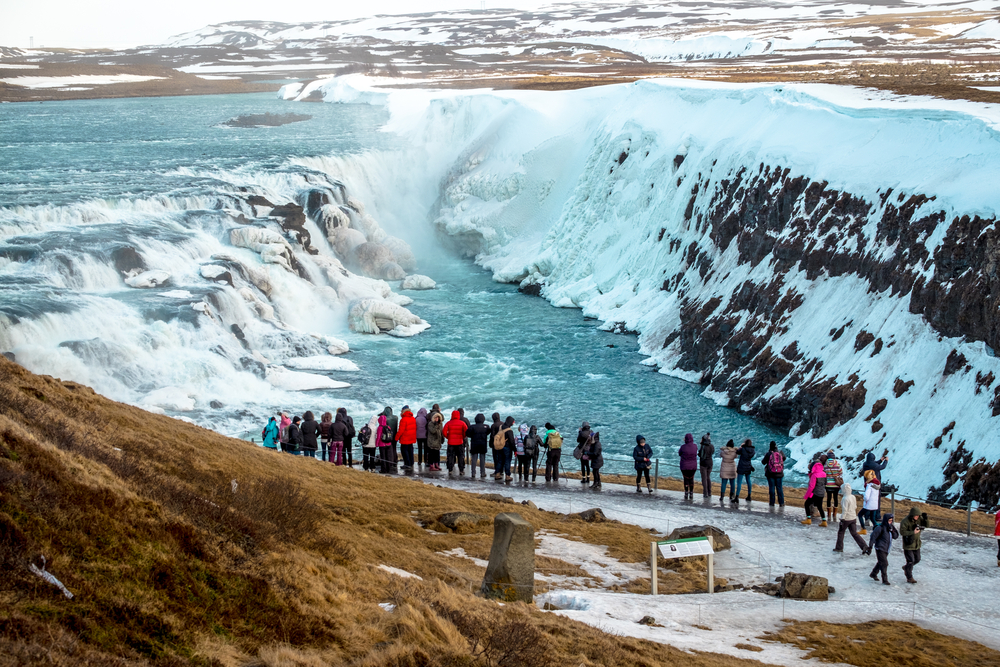 people standing and looking at gullfoss waterfall in winter