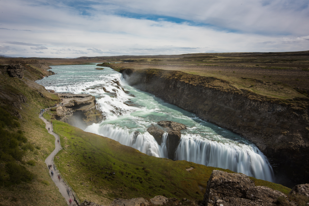 people walking on path at gullfoss in iceland on a sunny day