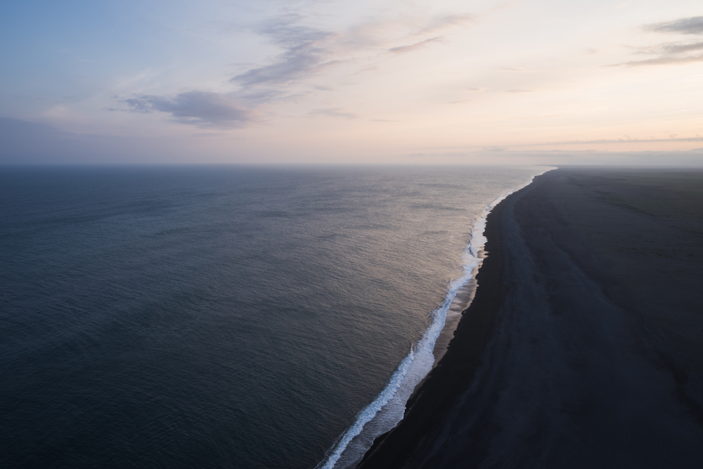 overlooking a black sand beach in iceland at sunset