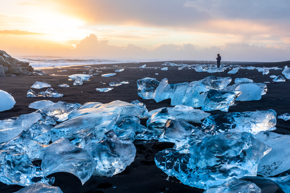 Person standing on Diamond Beach in Iceland at sunset